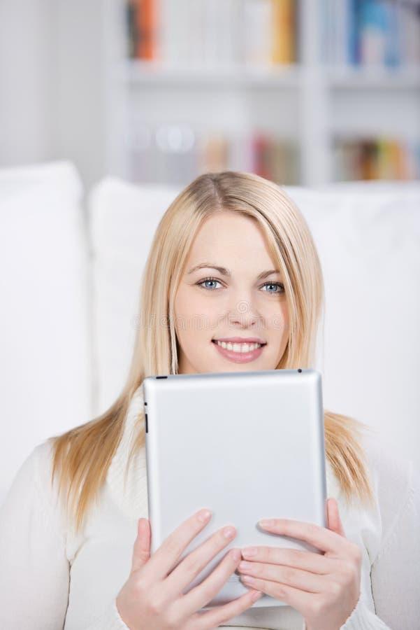 Ung kvinna som rymmer den Digital minnestavlan arkivfoto
