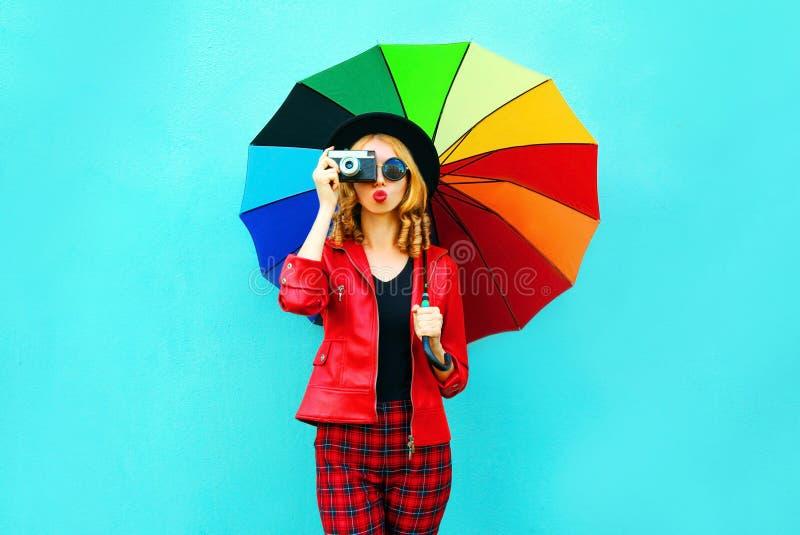 Ung kvinna som rymmer det färgrika paraplyet, retro kamera som tar bilden i det röda omslaget, svart hatt på den blåa väggen arkivfoton