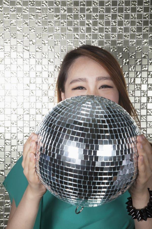 Ung kvinna som rymmer en diskoboll som framme ser kameran av den skinande väggen royaltyfria foton