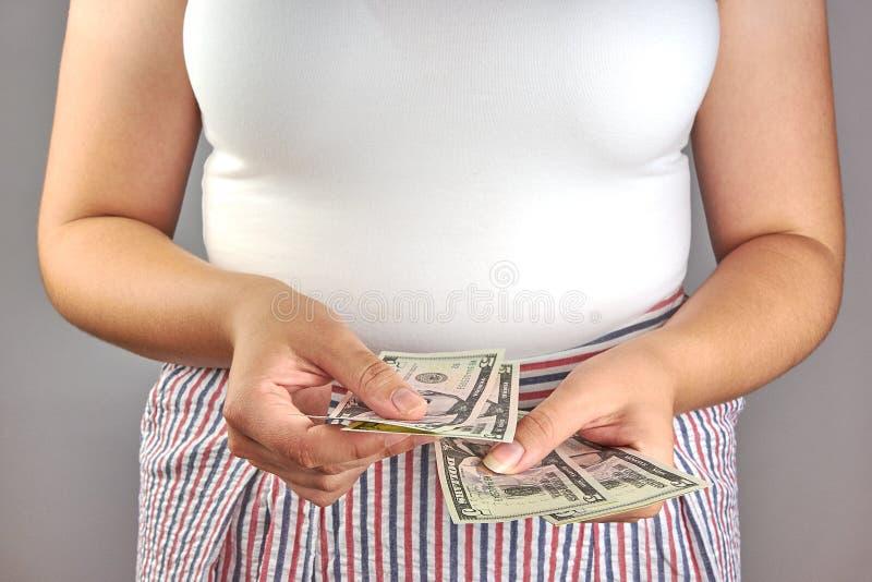 Ung kvinna som rymmer en dollarsedel i hand royaltyfri foto
