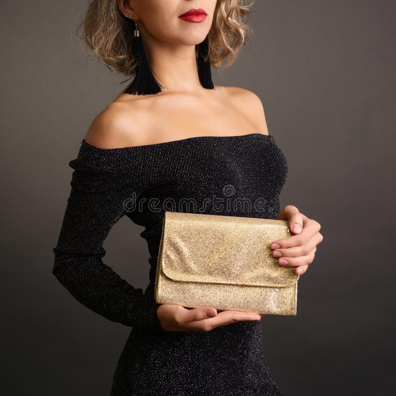 Ung kvinna som rymmer en guld- koppling isolerad på bakgrund royaltyfria bilder