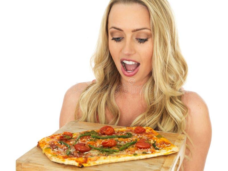 Ung kvinna som rymmer en helhet bakad pizza på ett träportionbräde royaltyfri fotografi