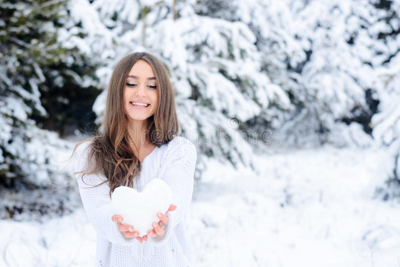 Ung kvinna som rymmer en hjärta från det insnöat vinterskogen royaltyfri foto