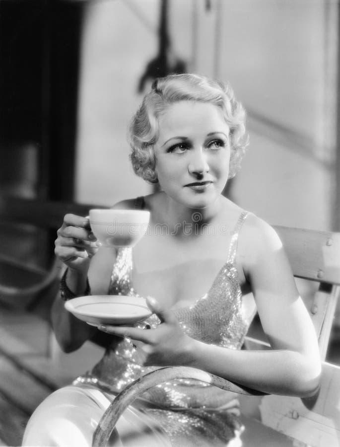 Ung kvinna som rymmer en kopp te (alla visade personer inte är längre uppehälle, och inget gods finns Leverantörgarantier som the arkivfoto