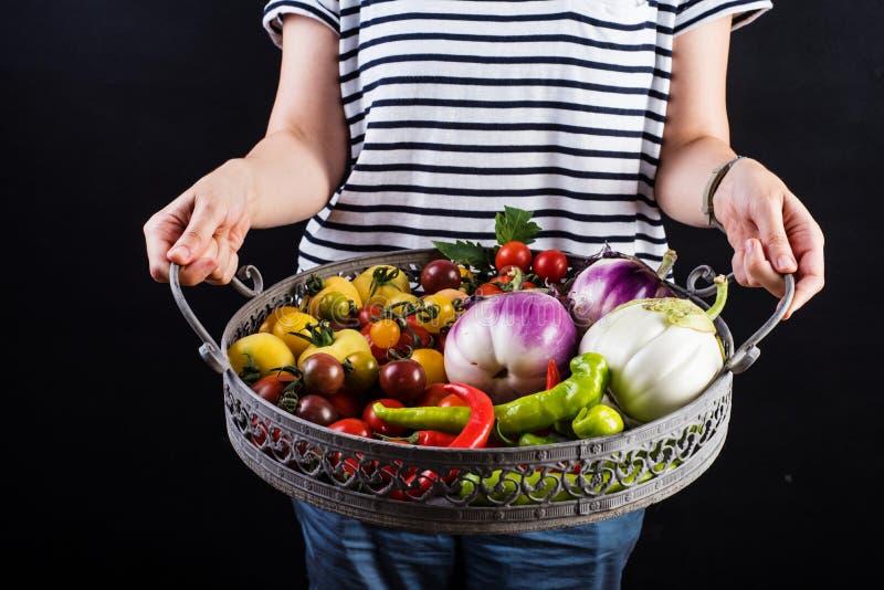 Ung kvinna som rymmer en korg full av veggies royaltyfri foto