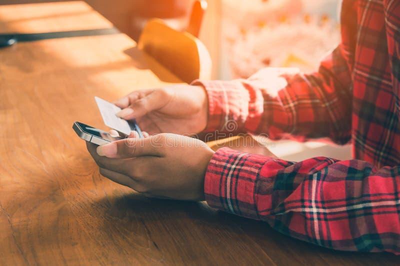 Ung kvinna som rymmer en kreditkort för att inhandla online-shopping royaltyfri fotografi