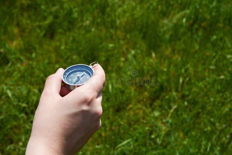 Ung kvinna som rymmer en magnetisk kompass i hennes hand och söker efter vägen Ut ur fokusgräsbakgrund arkivfoto