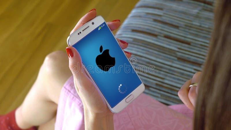 Ung kvinna som rymmer en mobiltelefon med att ladda den Apple mobilen app Begreppsmässig ledareCGI royaltyfria bilder