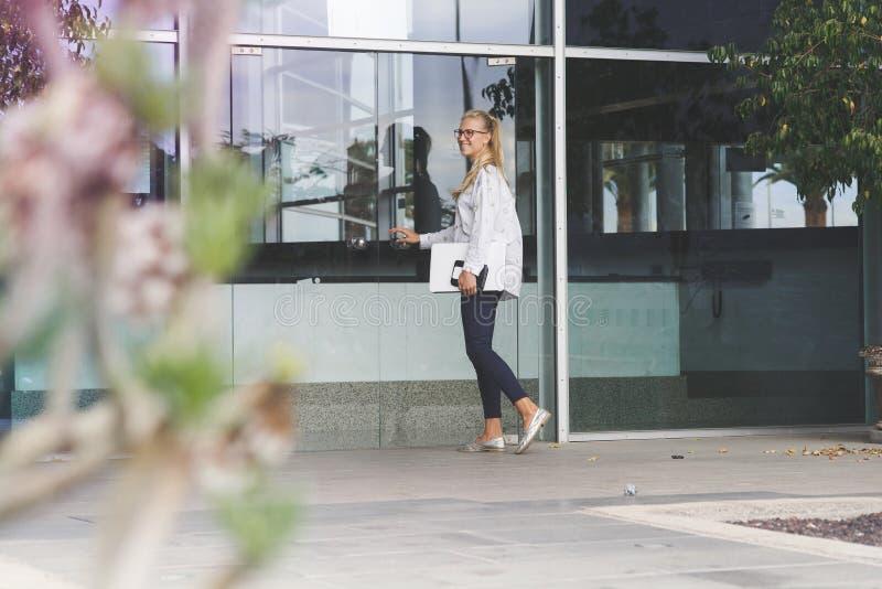 Ung kvinna som rymmer en vit bärbar dator och skriver in en byggnad fotografering för bildbyråer