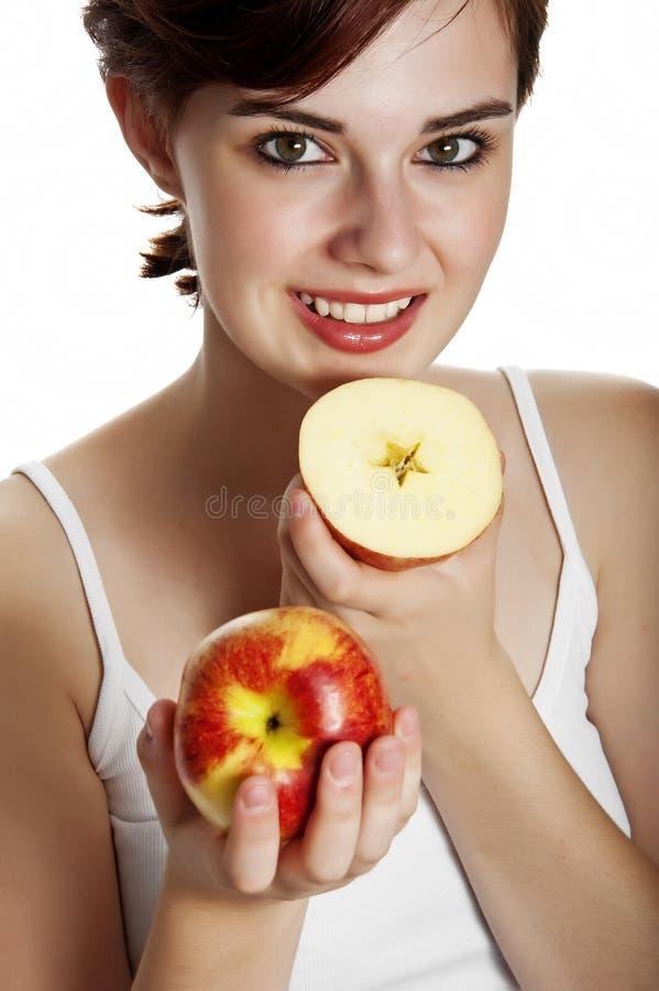 Ung kvinna som rymmer ett äpple royaltyfria foton