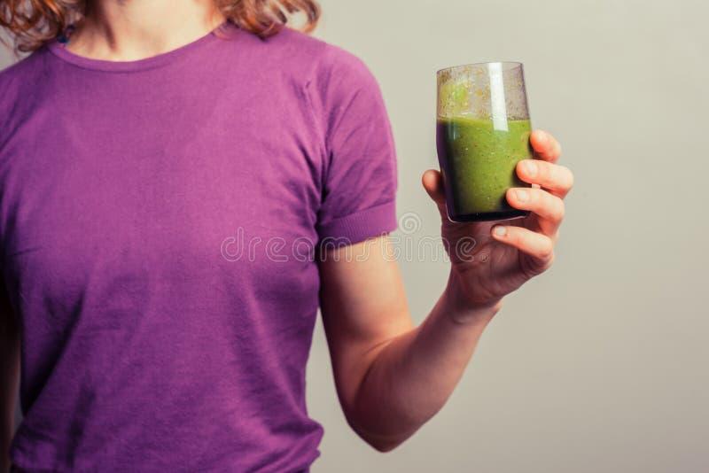 Ung kvinna som rymmer ett exponeringsglas av den gröna smoothien royaltyfri foto