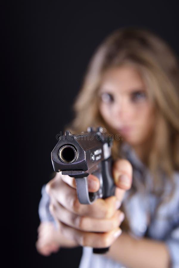Ung kvinna som rymmer ett vapen royaltyfria foton