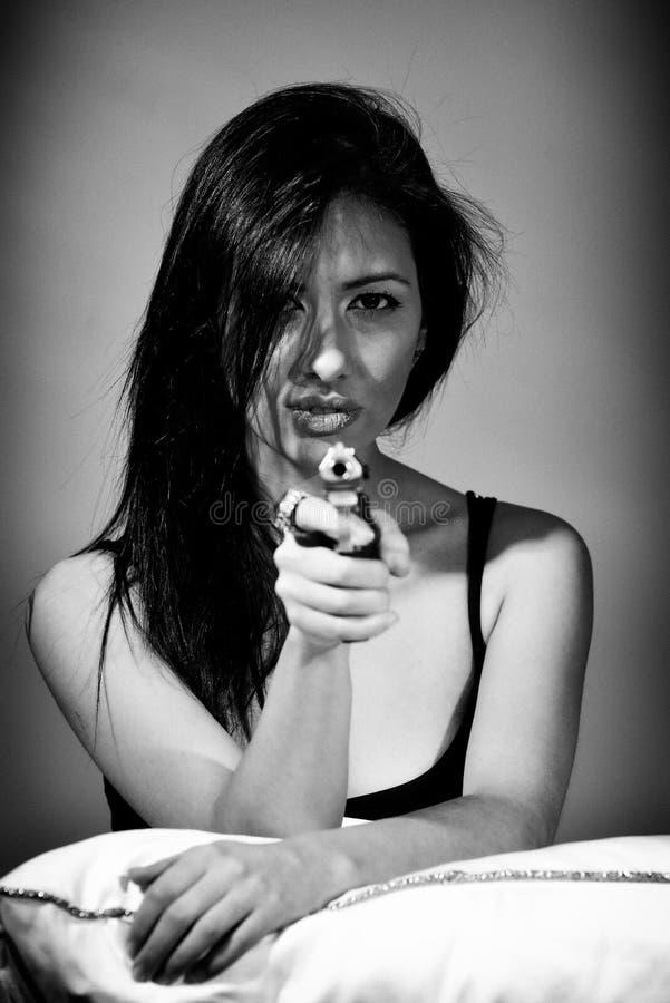 Ung kvinna som rymmer ett vapen arkivfoto