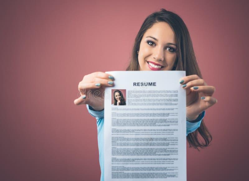 Ung kvinna som rymmer hennes meritförteckning arkivfoton
