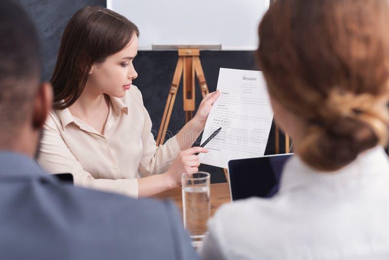 Ung kvinna som rymmer hennes meritförteckning under intervju royaltyfria bilder