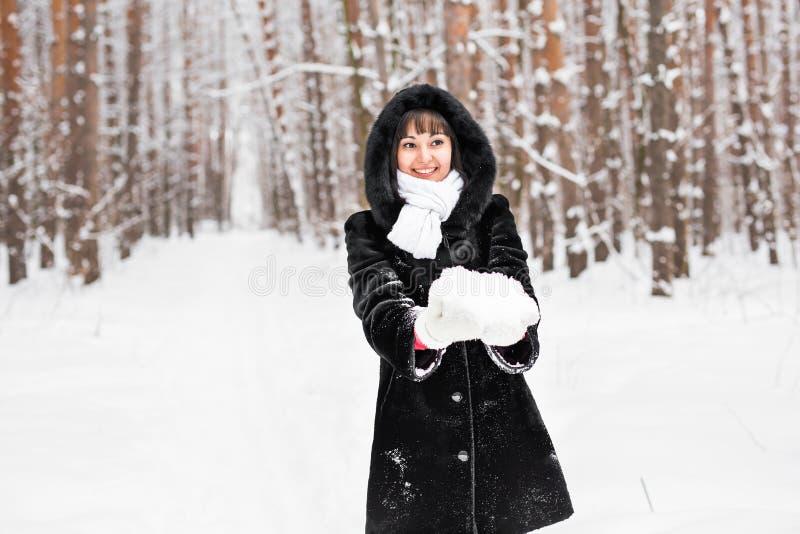 Ung kvinna som rymmer naturligt mjukt vitt insnöat hennes händer för att göra en kasta snöboll som ler under en kall vinterdag i arkivbild