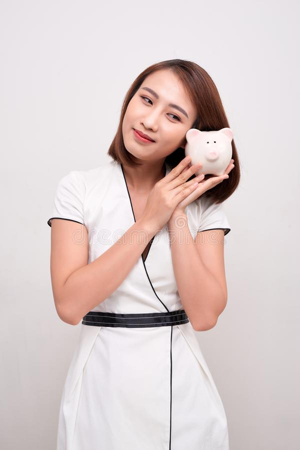 Ung kvinna som rymmer piggybank på vit bakgrund royaltyfri fotografi