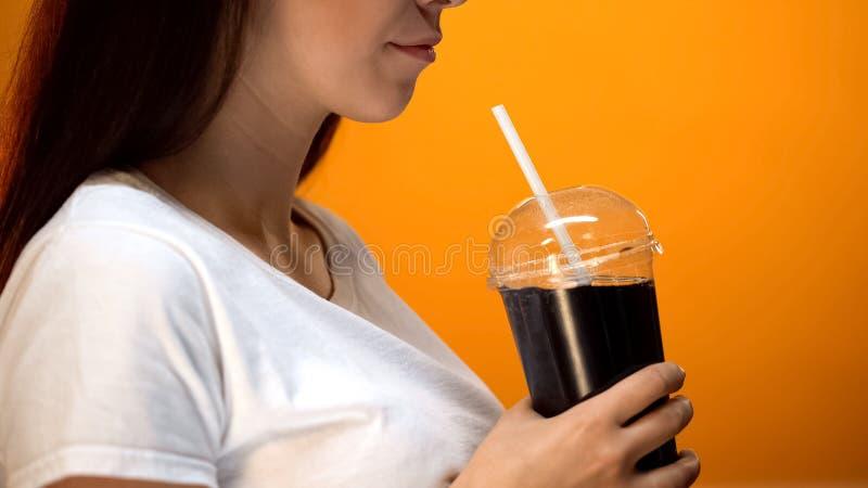 Ung kvinna som rymmer sodavatten och ler, sockerböjelse, höga kaloridrycker royaltyfri bild
