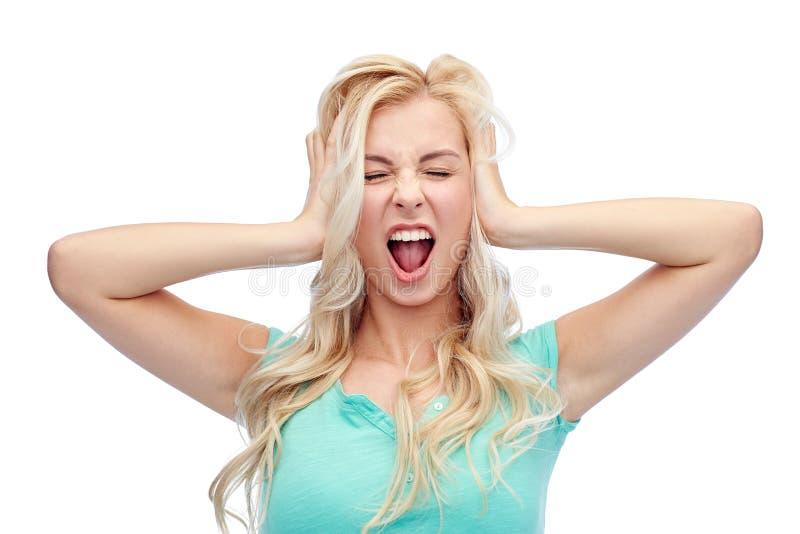 Ung kvinna som rymmer till hennes huvud och skrika royaltyfri fotografi