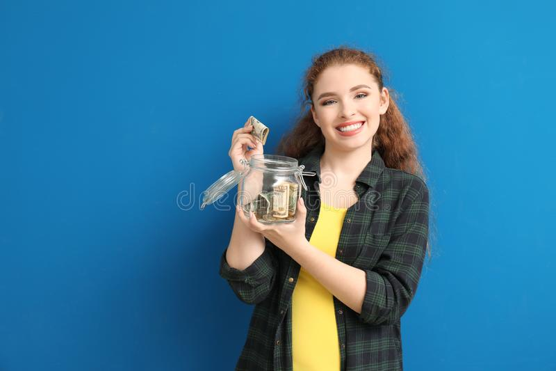 Ung kvinna som sätter dollarsedeln in i exponeringsglaskruset med pengar på färgbakgrund besparingar f?r pengar f?r flaskbegrepps arkivfoto