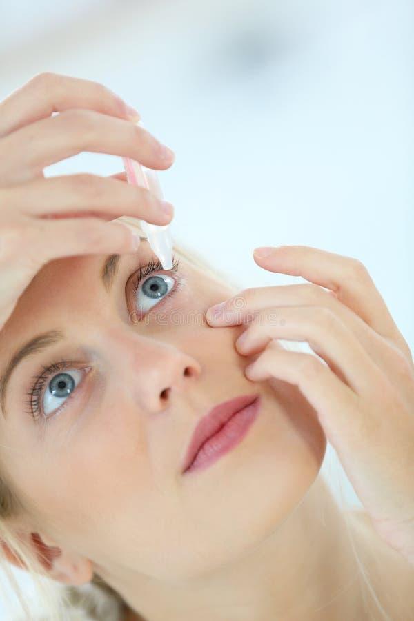 Ung kvinna som sätter i kontaktlinser royaltyfria bilder