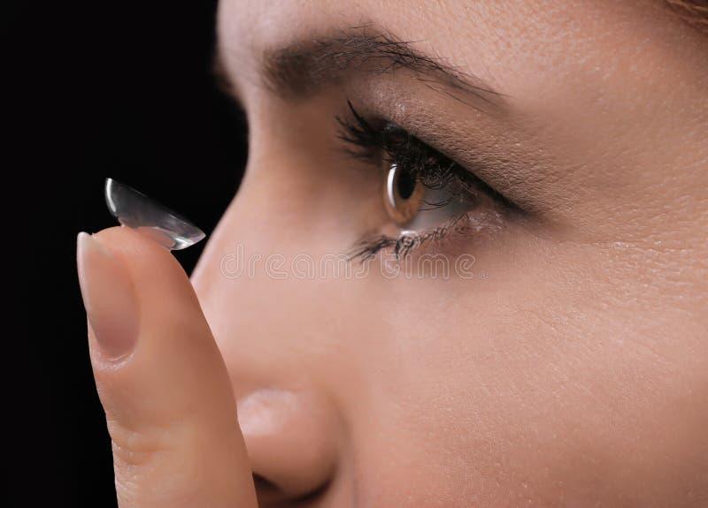 Ung kvinna som sätter kontaktlinsen arkivfoton