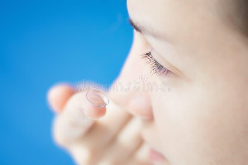 Ung kvinna som sätter kontaktlinsen i hennes öga fotografering för bildbyråer