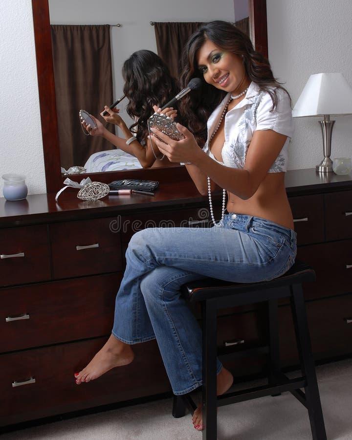 Ung kvinna som sätter på makeup arkivbild