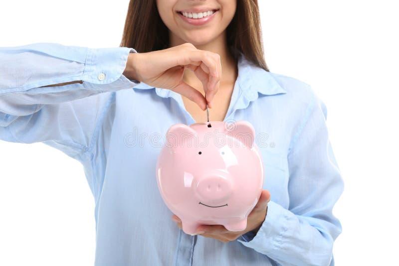 Ung kvinna som sätter pengar in i spargrisen på vit bakgrund, closeup royaltyfria bilder