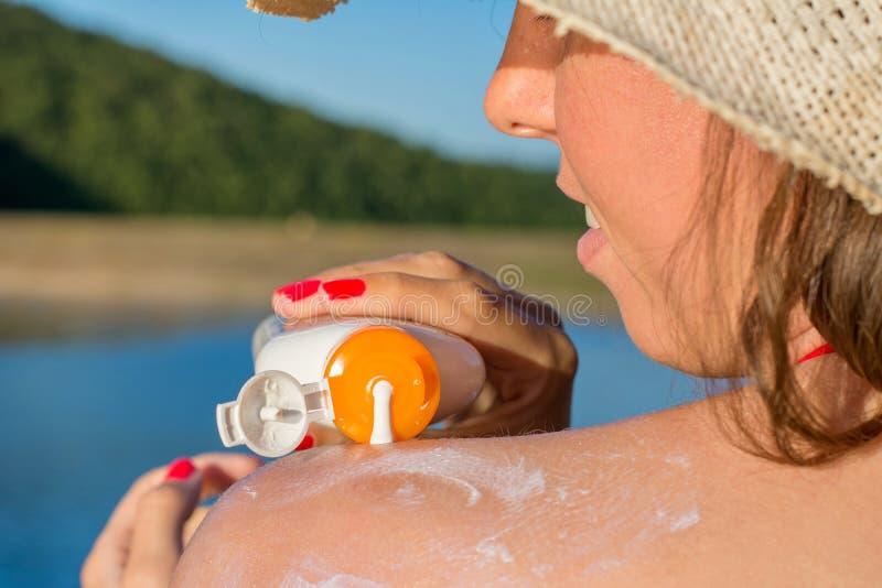 Ung kvinna som sätter sollotion på sommarsemester arkivbilder