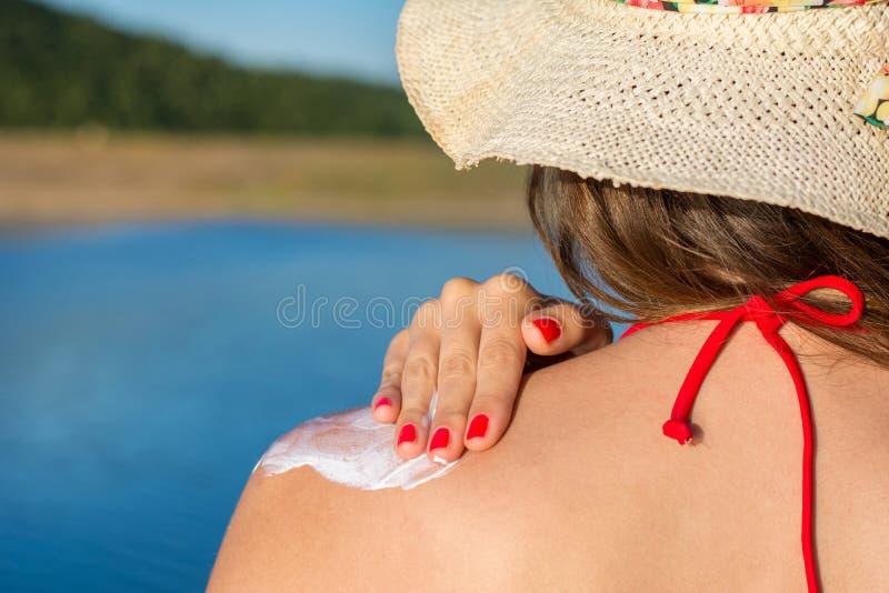 Ung kvinna som sätter sollotion på sommarsemester arkivfoton