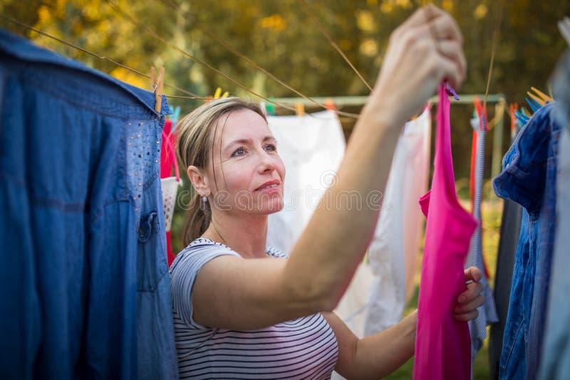 Ung kvinna som sätter tvätterit på ett rep i hennes trädgård royaltyfria bilder