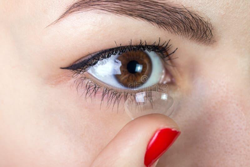 Ung kvinna som sätter upp kontaktlinsen i hennes ögonslut arkivfoton