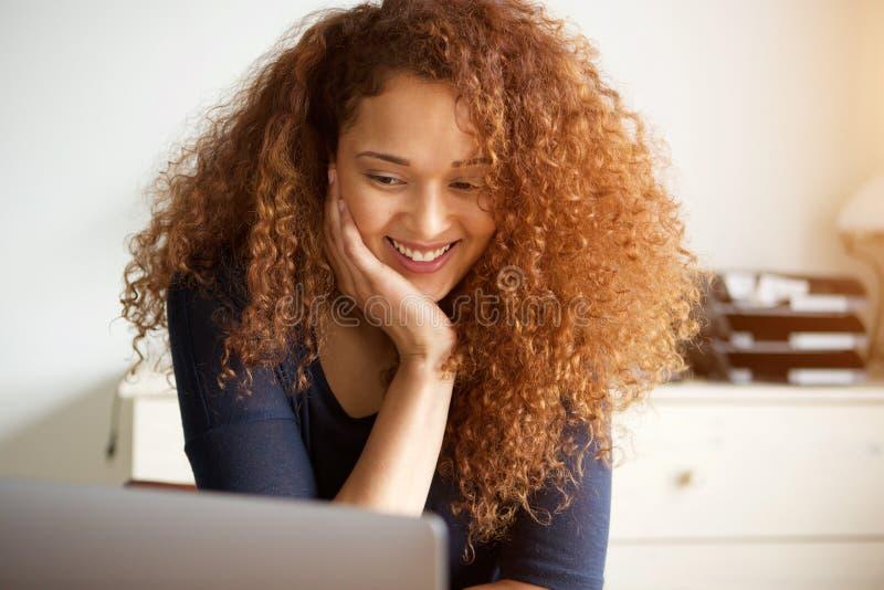 Ung kvinna som ser bärbar datordatorskärmen arkivbild