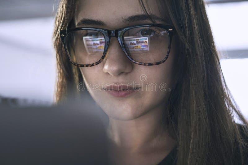 Ung kvinna som ser datorskärmen arkivbild