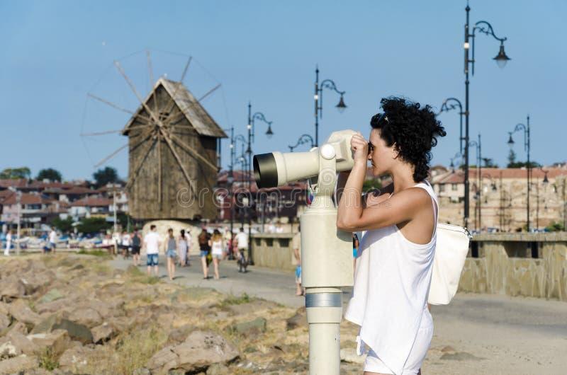 Ung kvinna som ser den fantastiska sikten till och med ett mynt som är binokulärt i en observationspunkt i Bulgarien fotografering för bildbyråer