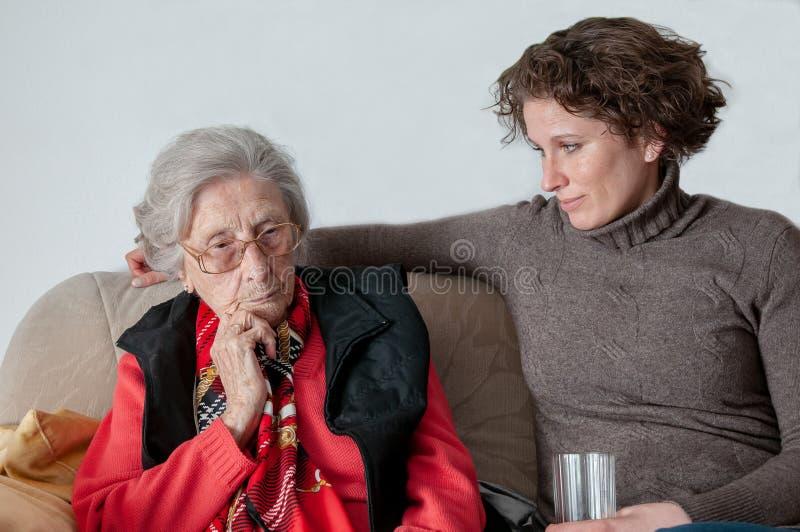 Ung kvinna som ser den ledsna höga damen arkivbild