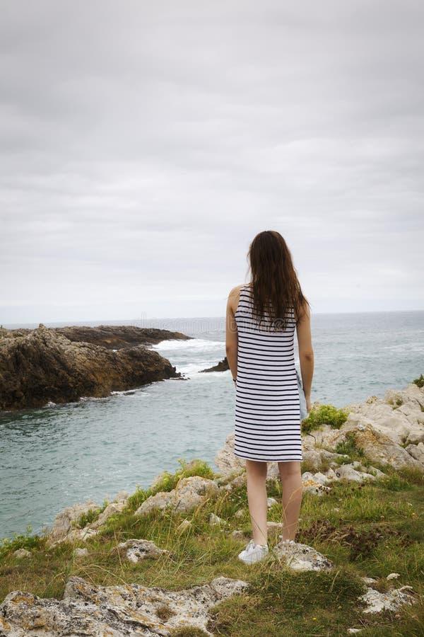 Ung kvinna som ser en ensam och härlig stenig kust royaltyfria foton