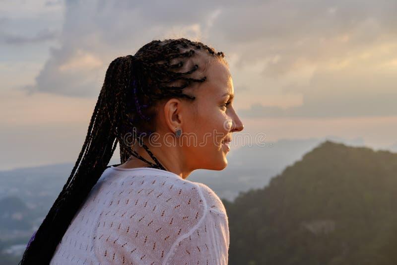 Ung kvinna som ser f?rbluffa solnedg?ng i berg Cornrows frisyr royaltyfri fotografi