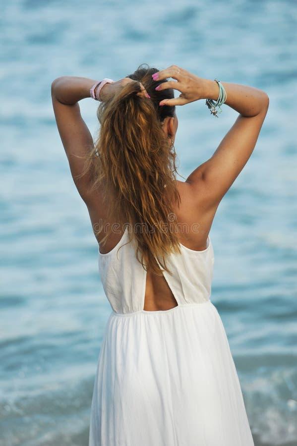 Ung kvinna som ser havsvatten i sommarferie som tar hästsvansen på hennes hår som tycker om den kopplade av semestern royaltyfria foton
