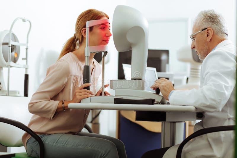 Ung kvinna som ser in i special utrustning för ögondiagnostik royaltyfri bild