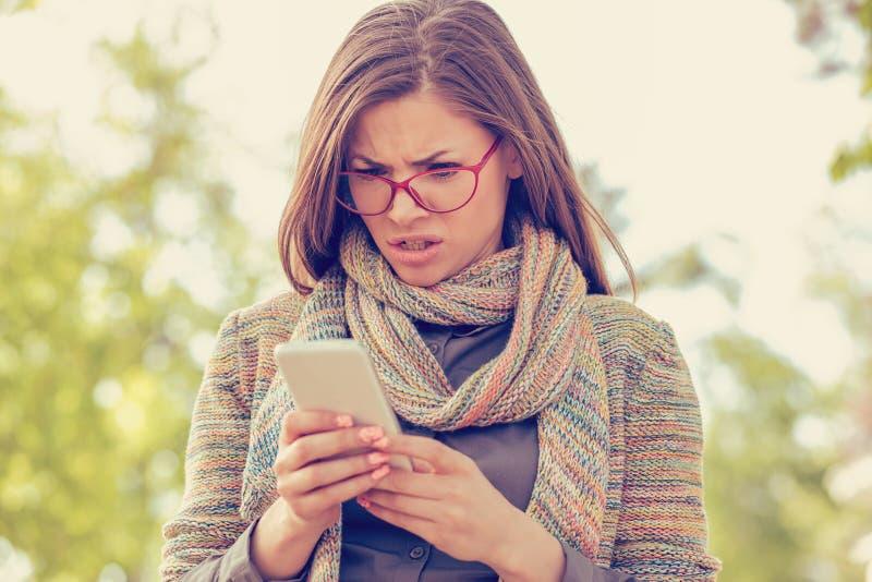 Ung kvinna som ser ilsken på telefonen arkivfoton
