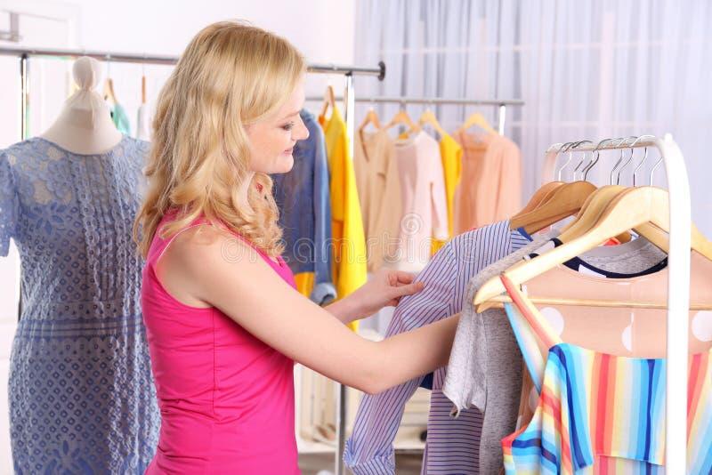 Ung kvinna som ser kläder på kuggen arkivbild