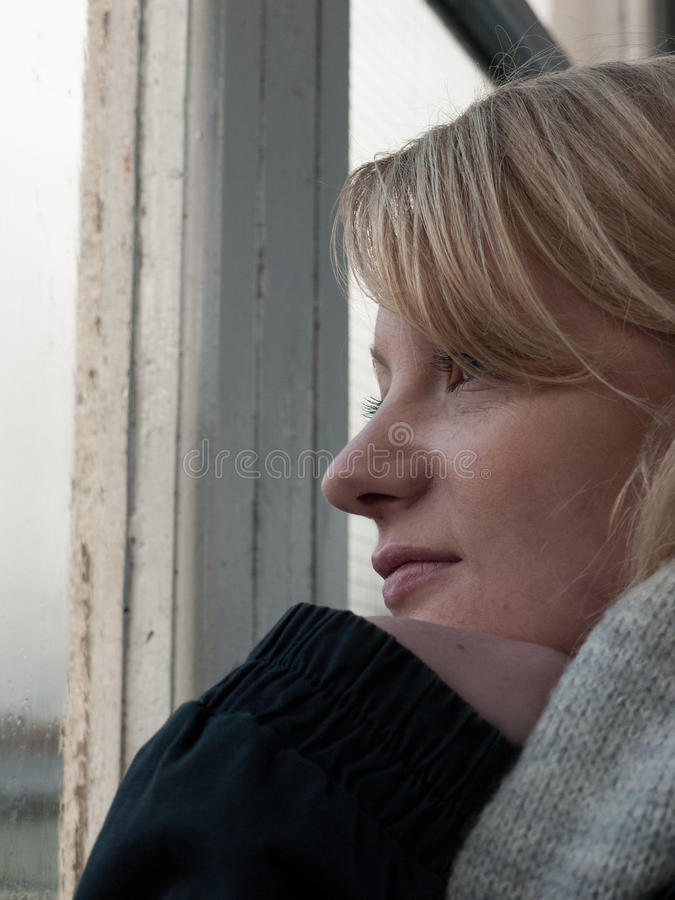 Ung kvinna som ser ut ur ett fönster arkivbild