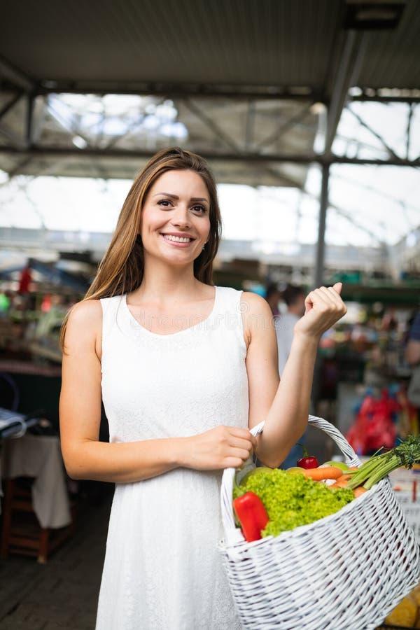Ung kvinna som shoppar sund mat på marknaden royaltyfria bilder