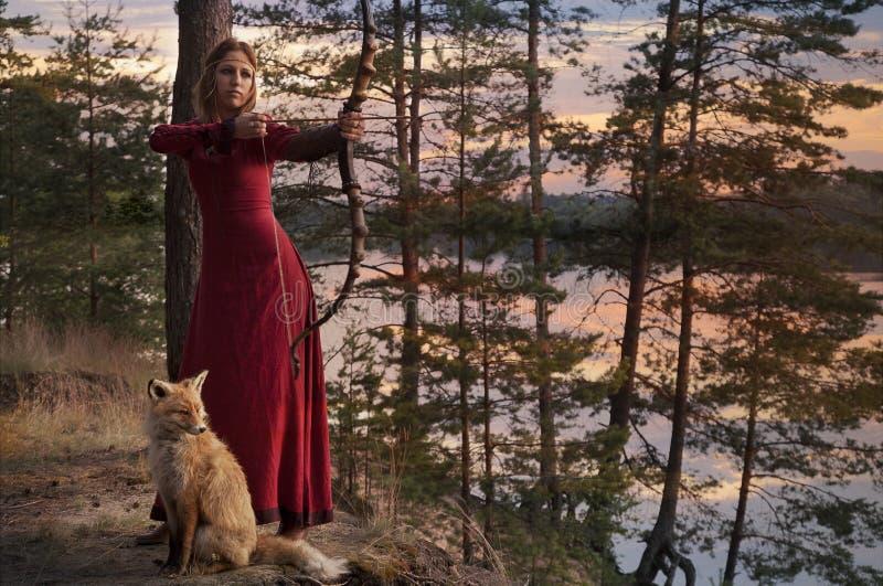 Ung kvinna som siktar med pilbågen och pilen royaltyfri fotografi