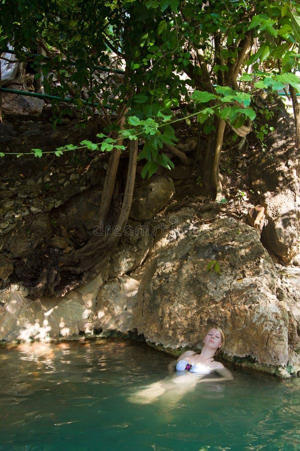 Ung kvinna som simmar i floden royaltyfri bild