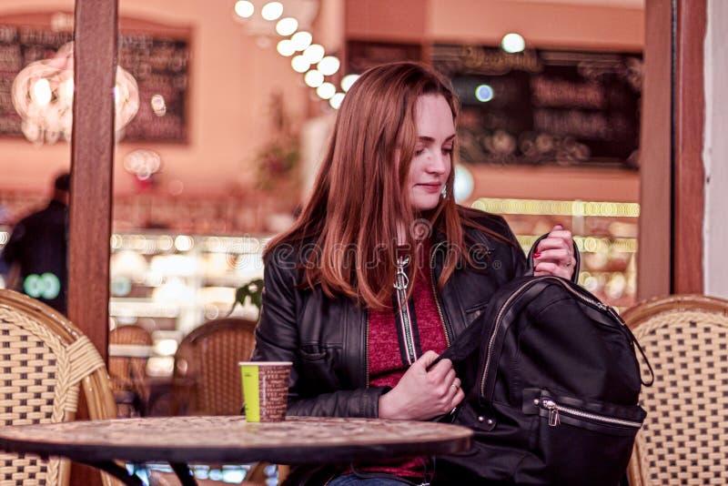 Ung kvinna som sitter i aftonen i ett kafé och ser för att svärta ryggsäcken arkivbild