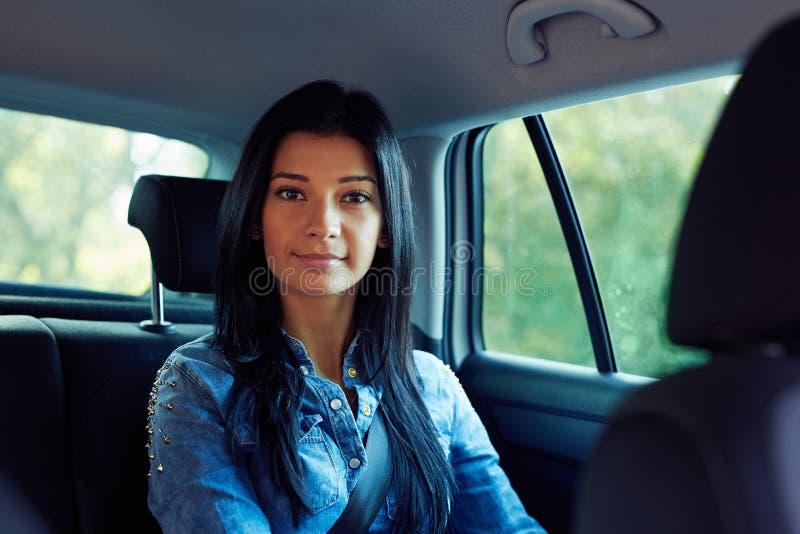 Ung kvinna som sitter i bilen royaltyfri foto