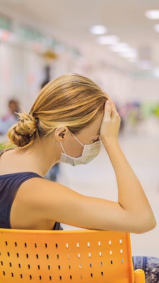 Ung kvinna som sitter i sjukhuset som väntar på en doktors tidsbeställning Patienter i det VERTIKALA FORMATET för doktorer väntan royaltyfri bild